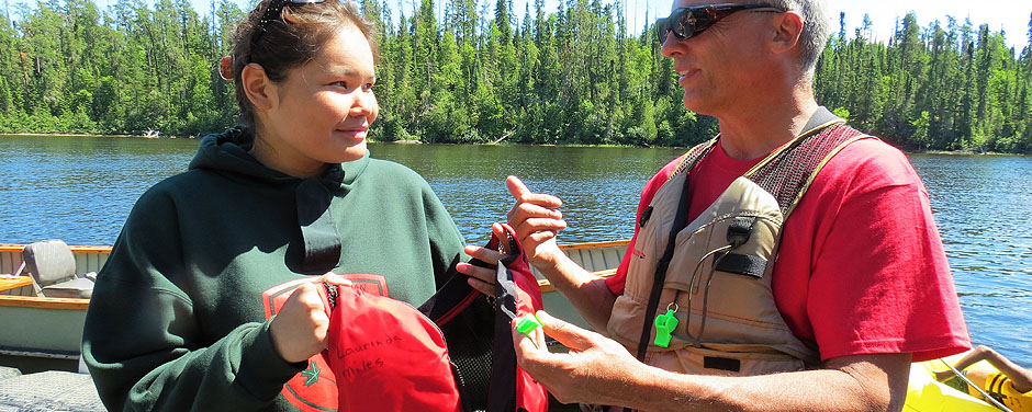Slide - Junior Canadian Ranger Laurinda Miles of Fort Severn First Nation in Northern Ontario, receives a life jacket from Gordon Giesbrecht