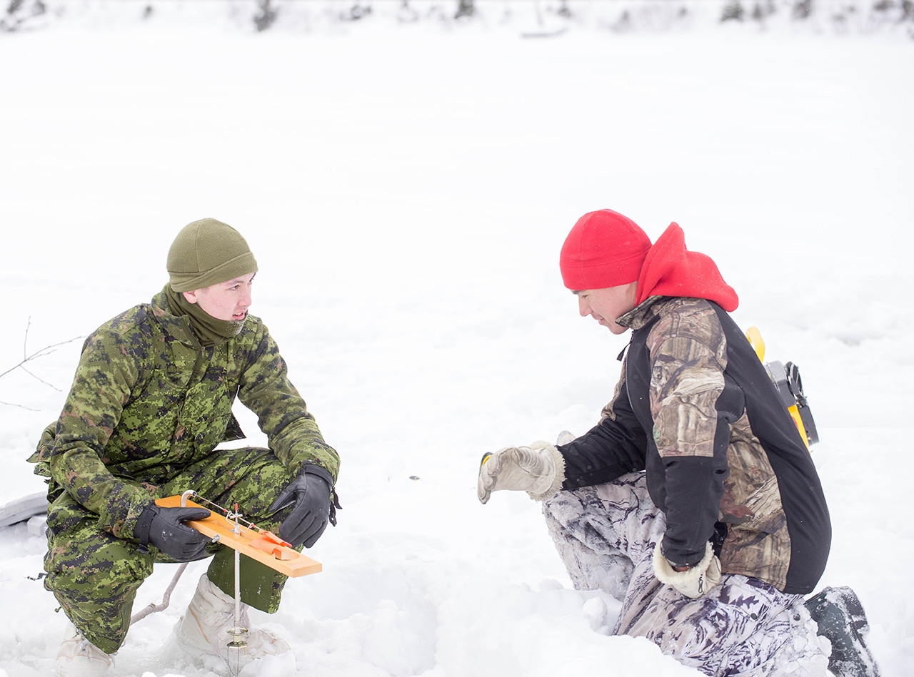 Ranger Brandon Nakogee from 3rd Canadian Ranger Patrol Group teaches Corporal Benjamin Stephenson from the Algonquin Regiment how to ice fish during Exercise MOOSE SURVIVAL in Cobalt Ontario, February 7, 2015.