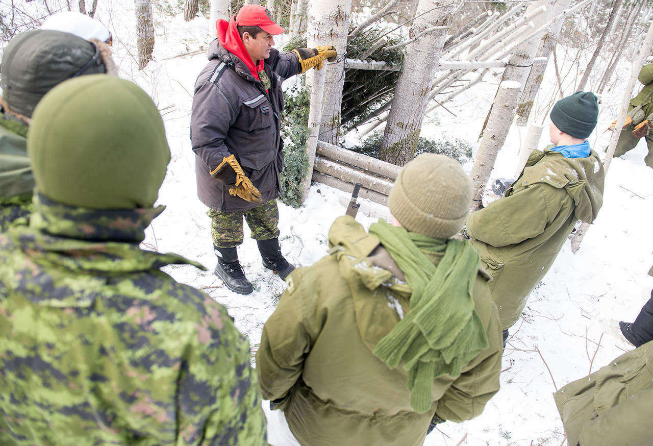 Master Corporal Joe Lazarus of 3 Canadian Ranger Patrol Group demonstrates an improvised shelter to members of the Algonquin Regiment and Army Cadets from northern Ontario during Exercise MOOSE SURVIVAL in Cobalt Ontario, February 7, 2015.