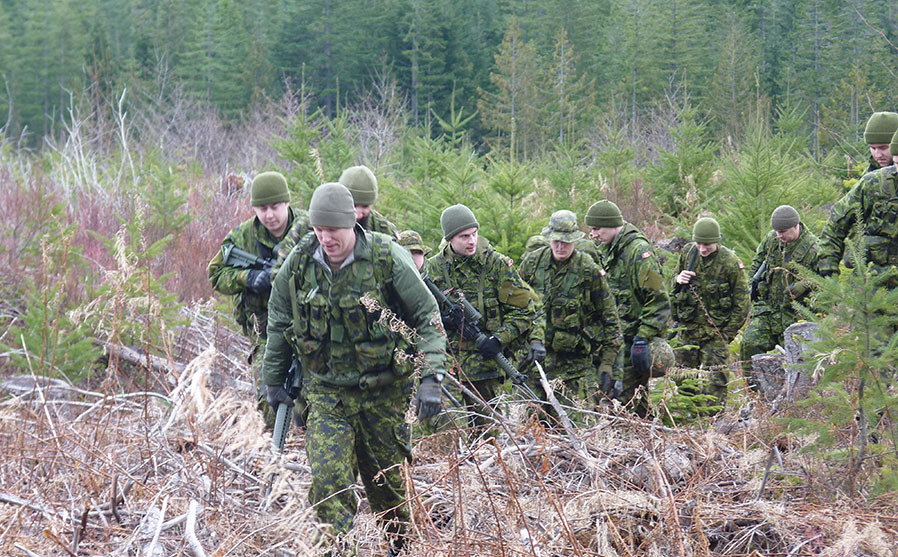 section of soldiers move through a clearing while moving between survival training stands as part of Exercise Coastal Sasquatch.