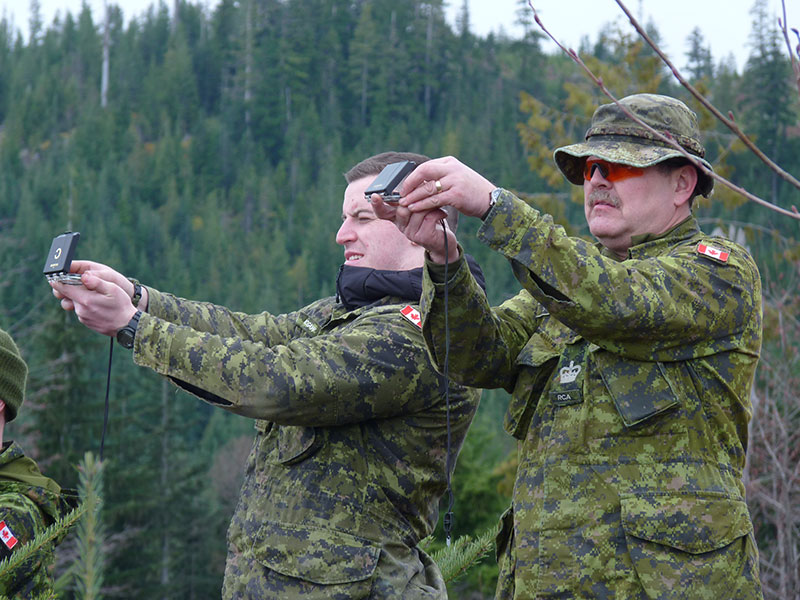 Corporal Frazer McGraw (left) of The Canadian Scottish Regiment (Princess Mary's) shoots a bearing using his compass, while his navigation instructor Warrant Officer Henry Slack of 5th (BC) Field Regiment  (right) confirms his accuracy as part of Exercise Coastal Sasquatch. Photo:  2Lt Cameron Park