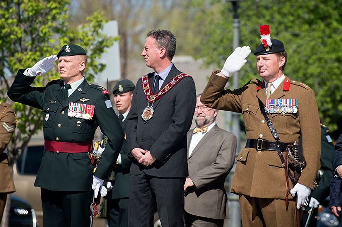Lt Col Sean Hackett (Left), Commander of Canadian Forces Base Suffield, and Col Landon (Right), Commander British Army Training Unit Suffield, stand alongside Medicine Hat Mayor Ted Clugston during the parade. Photo:  Corporal James McAllister (RLC)