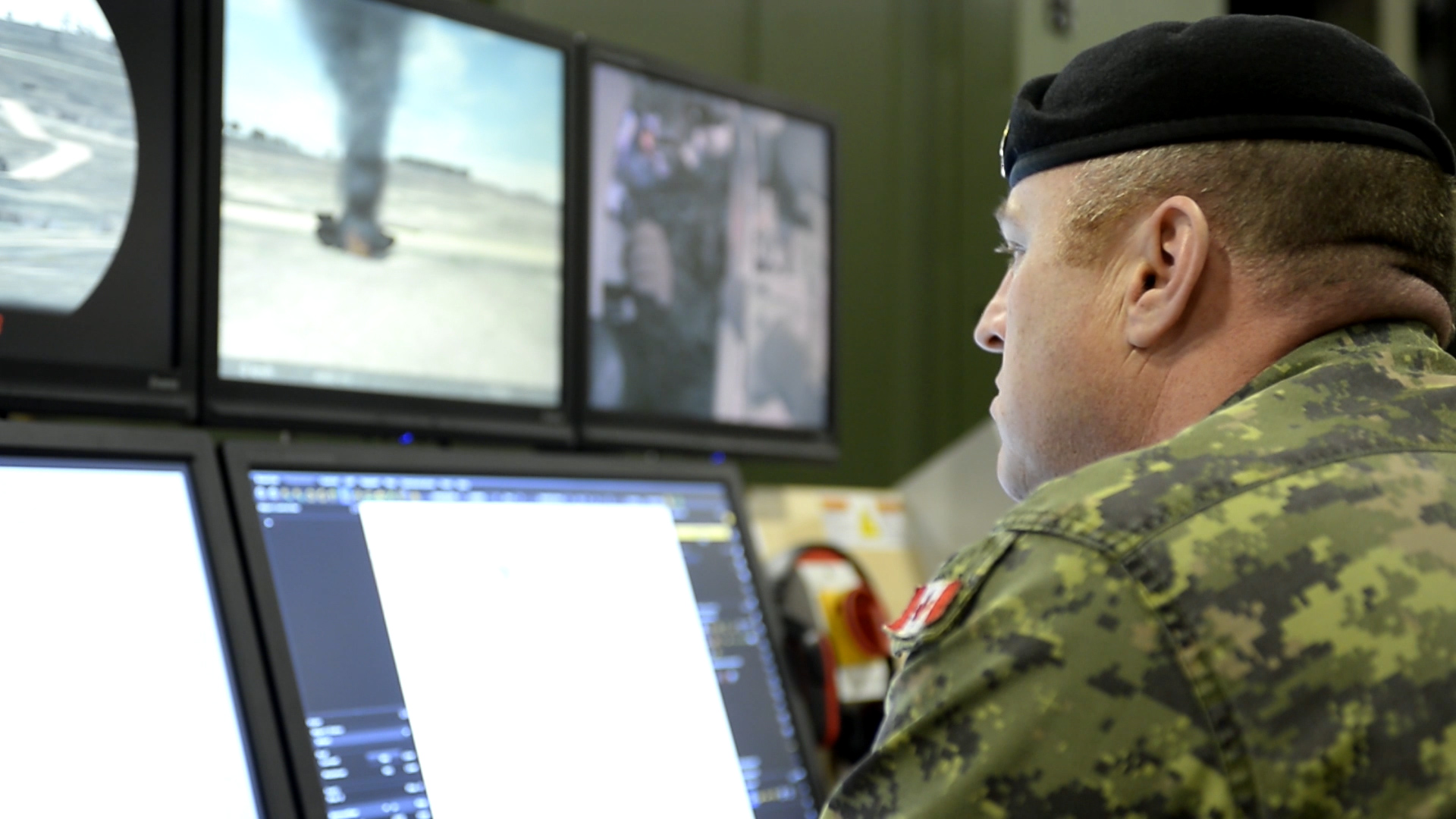An instructor monitors soldiers operating stationary Leopard-2 tank simulators at the Combat Training Centre, part of the Canadian Army Doctrine and Training Centre in Gagetown, New Brunswick in March, 2015. Photo by: Combat Training Centre