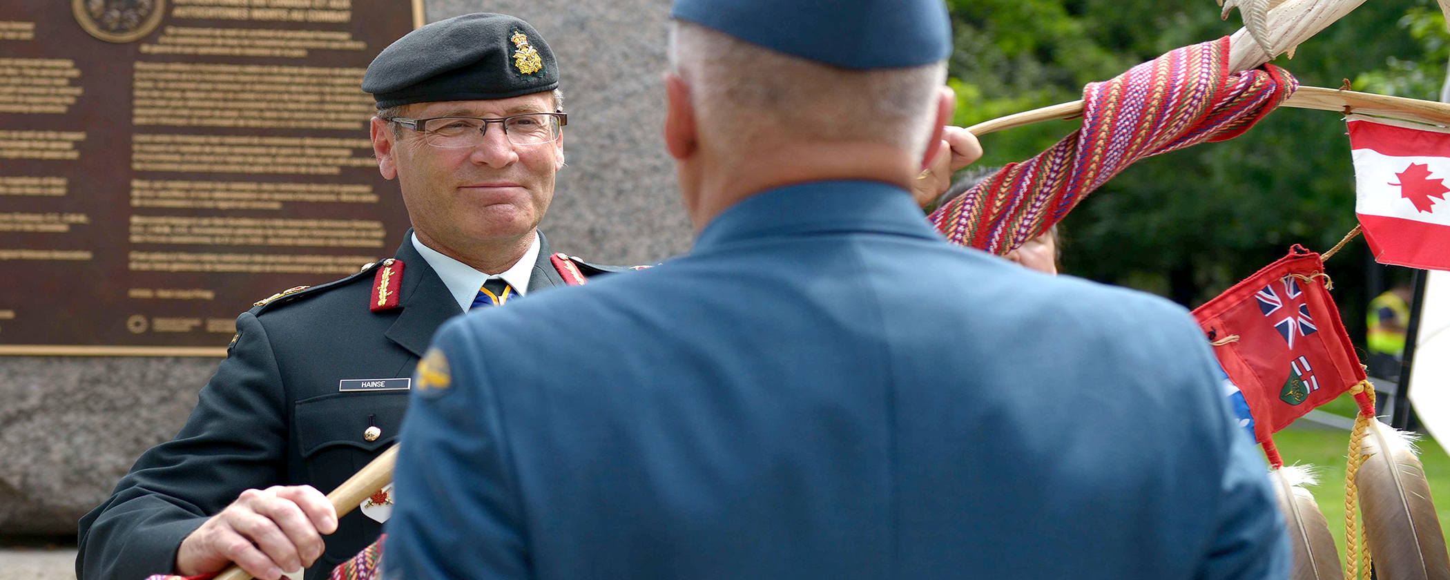 Two men in military uniform hold a large ceremonial First Nations staff