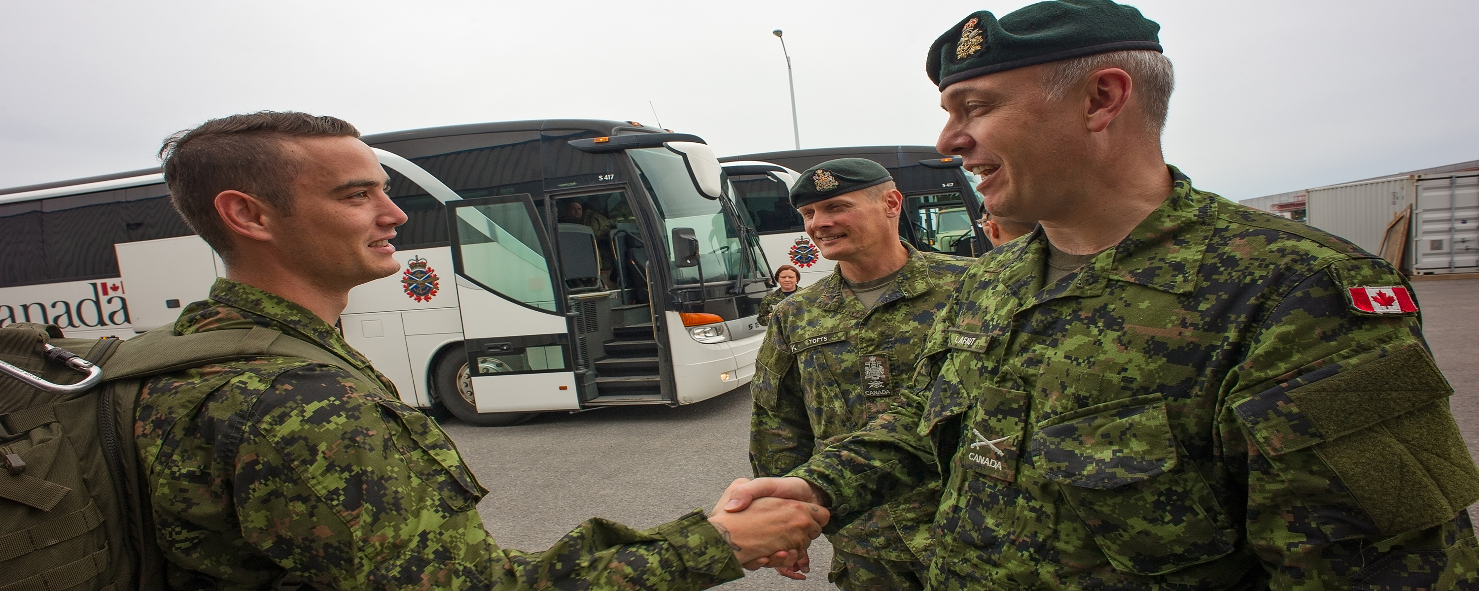 Two soldiers in uniform shake hands with another soldier in uniform as he prepares to board a white bus.