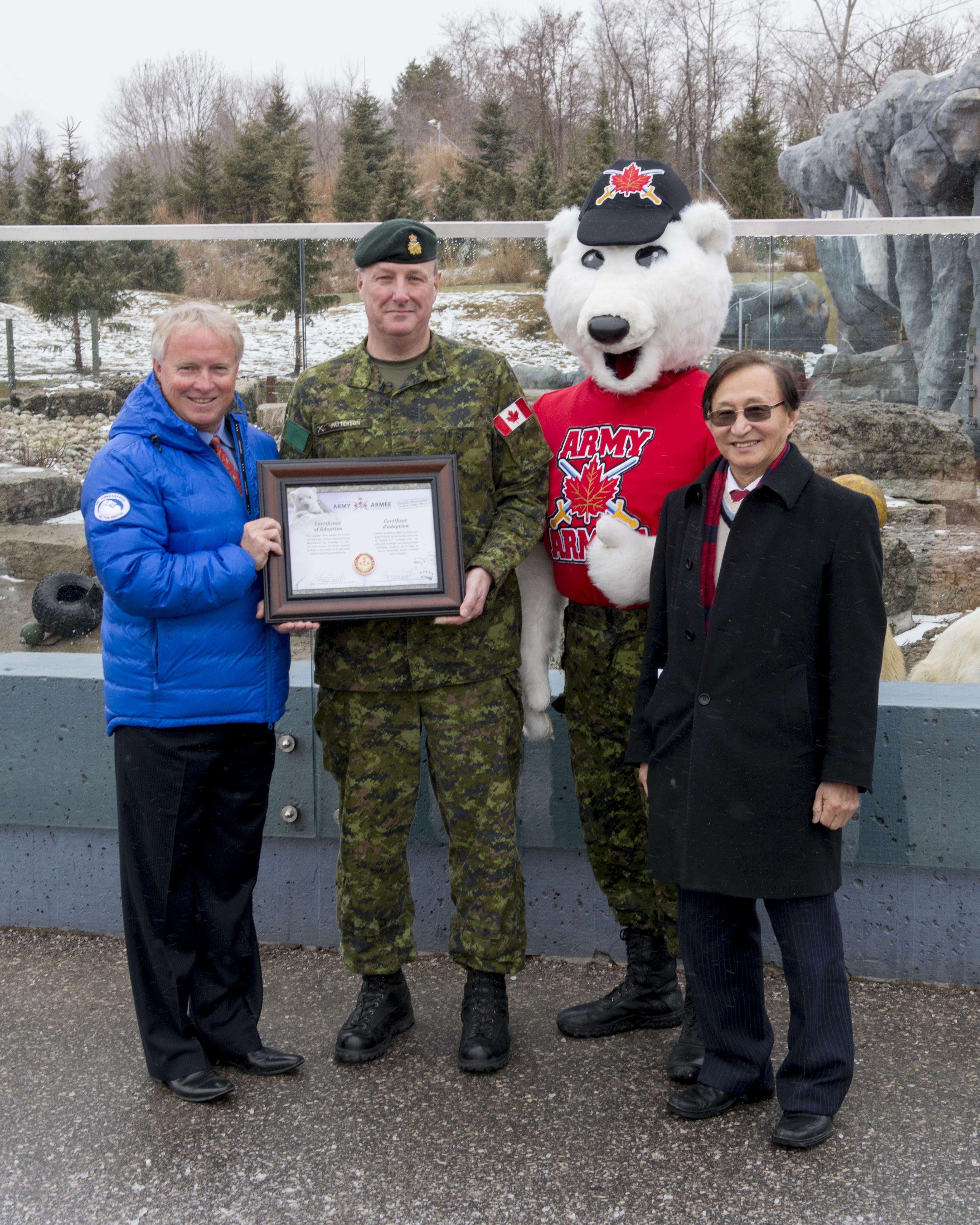 Brigadier-General David Patterson, Deputy Commander of the 4th Canadian Division, presents a certificate of adoption to Toronto Zoo officials John Tracogna, CEO, Toronto Zoo (left) and Raymond Cho, Chair, (right) at the Toronto Zoo during the welcoming of Private Juno, the polar bear cub, at Toronto Zoo on February 25, 2016. Photo by: MCpl Precious Carandang, 4th Canadian Division Public Affairs 2016 DND-MDN Canada.