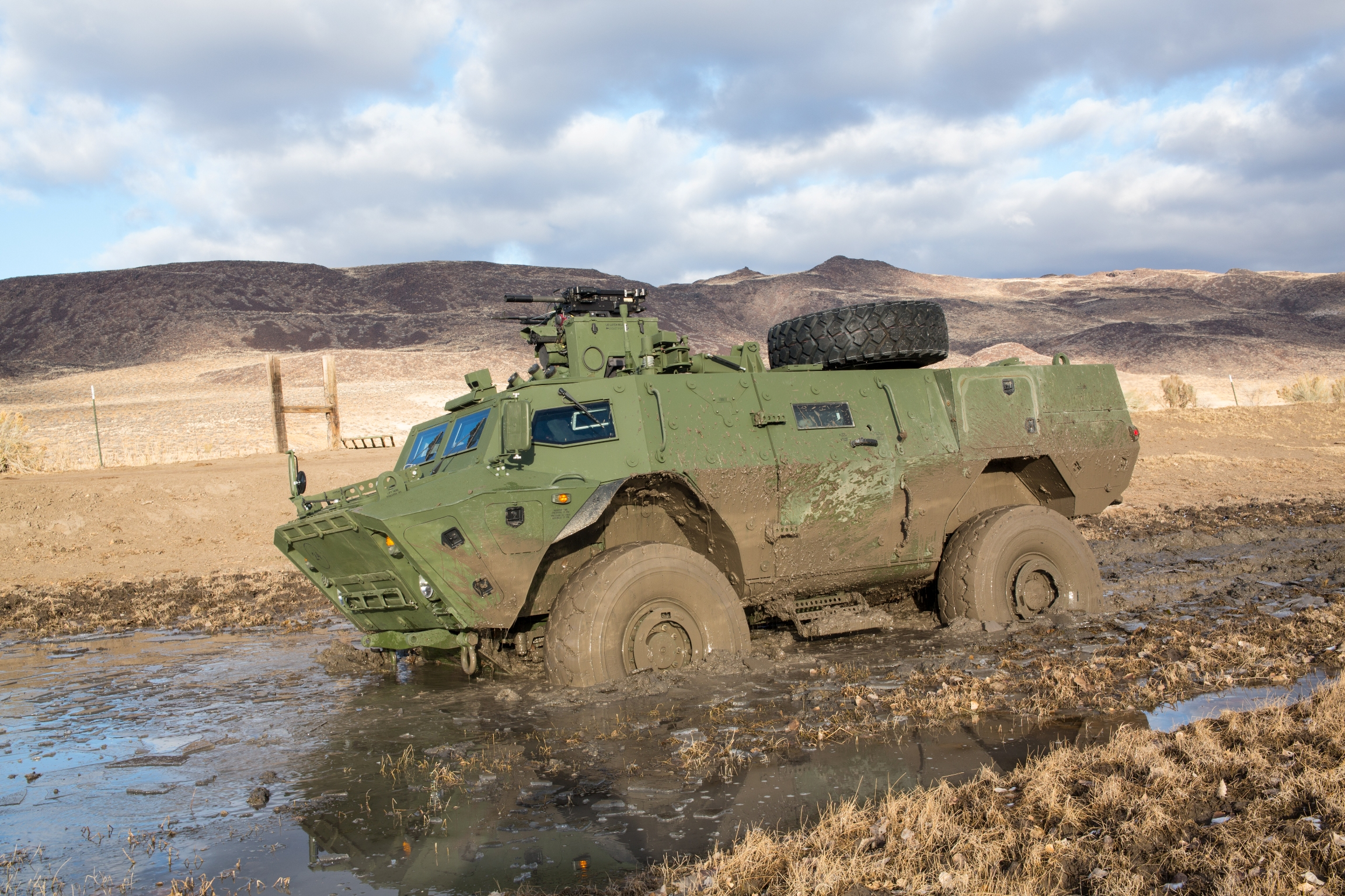 Side view of Tactical Armoured Patrol Vehicle in muddy terrain.