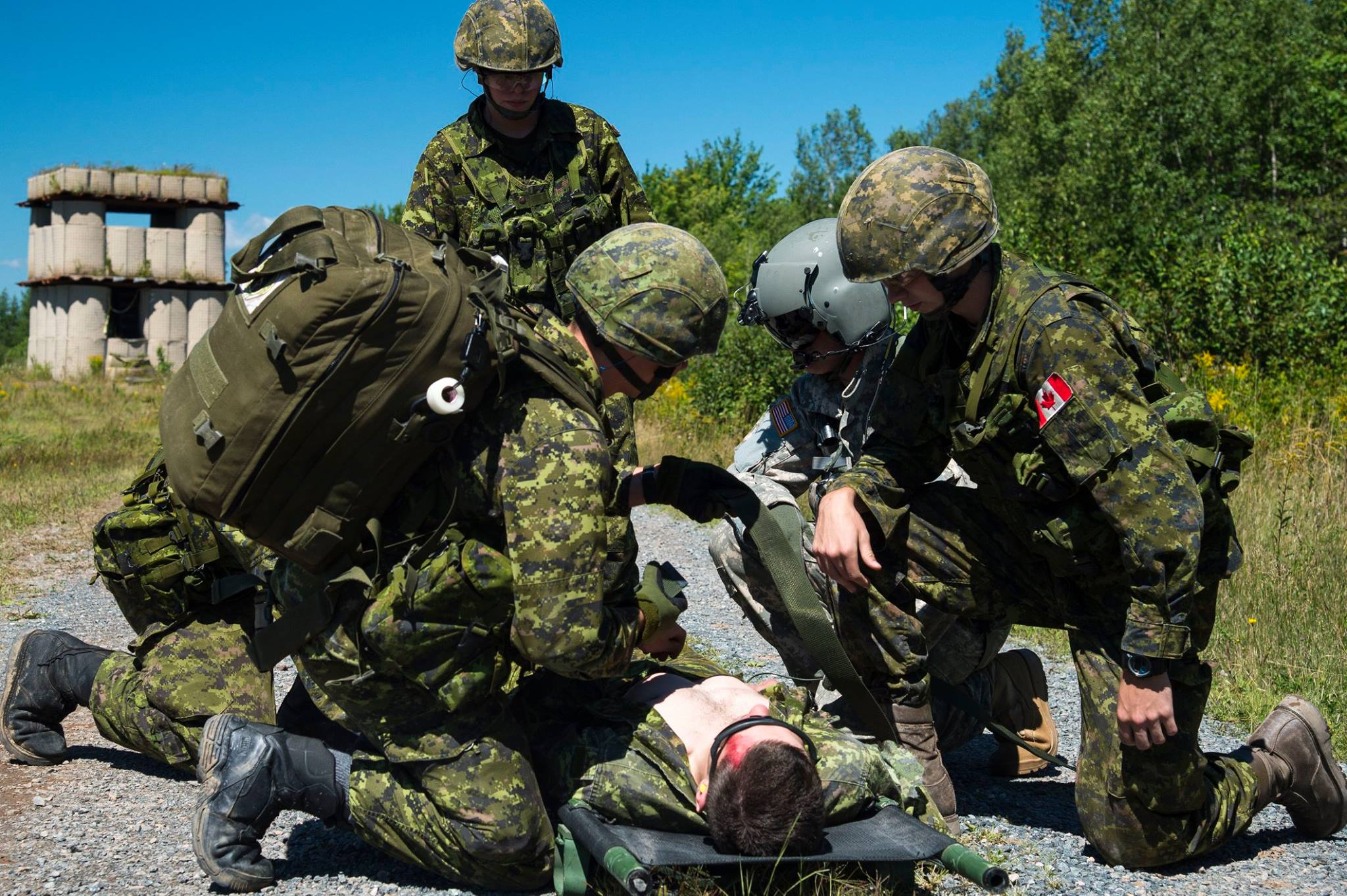 Military medics prepare to transfer a simulated casualty as part of a casualty exercise during Exercise STRIDENT TRACER at 5th Canadian Division Support Base Gagetown on August 23, 2016. ©2016 DND/MDN Canada. Photo by: Corporal Chris Ringius, Formation Imaging Section Halifax