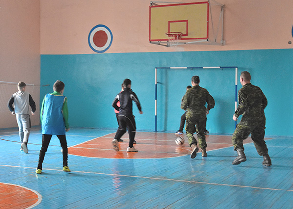 Two members of Joint Task Force – Ukraine on Op UNIFIER play soccer with local schoolchildren during a visit in honour of Ukraine's Defenders Day to Secondary School #98 in Lviv, Ukraine, on October 13, 2016.  Photo : Joint Task Force - Ukraine