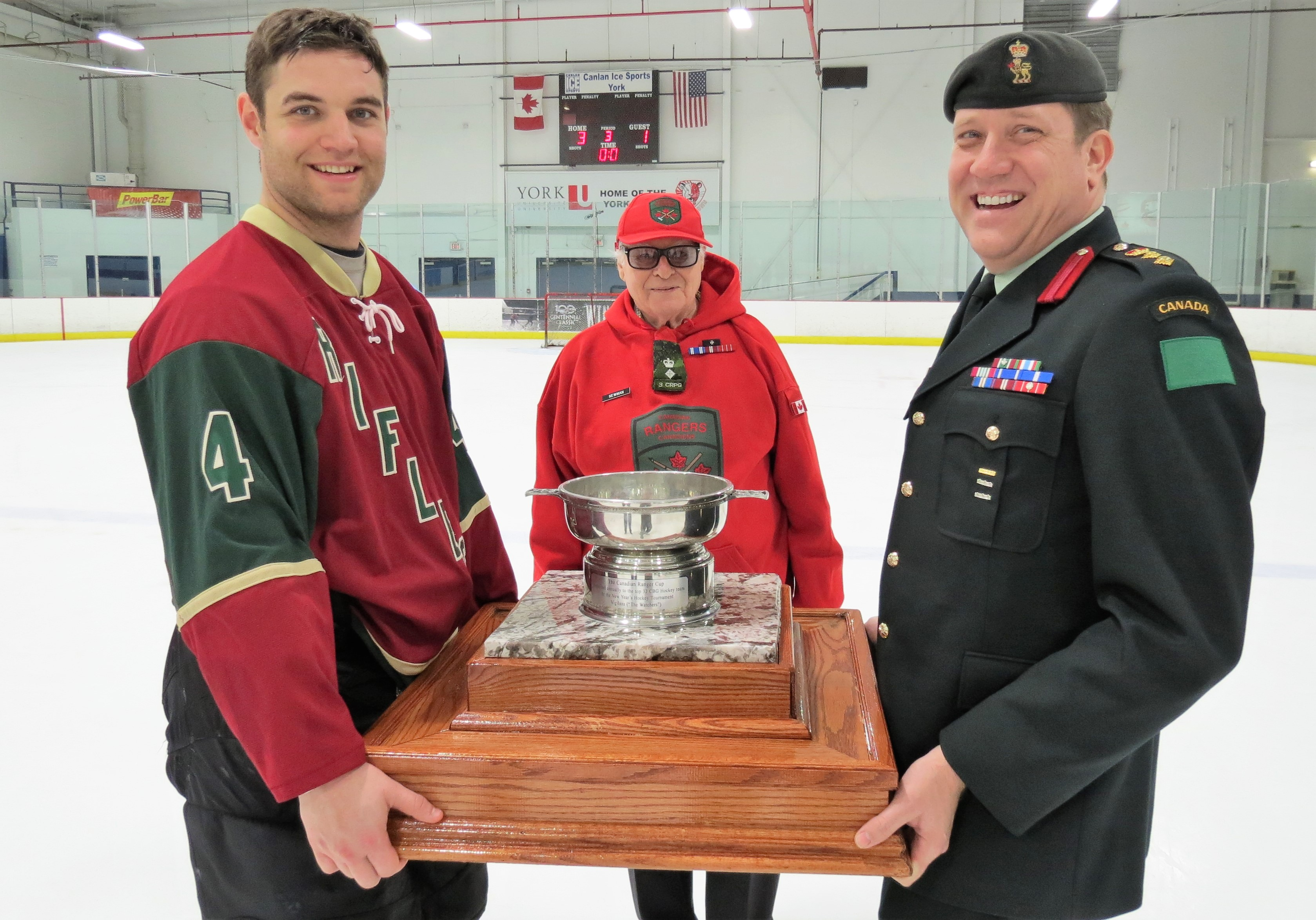 Master Corporal Justin Wright, left, captain of the winning Queen's Own Rifles of Canada team, holds the Ranger Foundation Cup with Colonel Dwayne Hobbs, assistant chief of staff at 4th Canadian Division. Hon. Lieutenant-Colonel John Newman of 3rd Canadian Ranger Patrol Group and chairman of the Ran