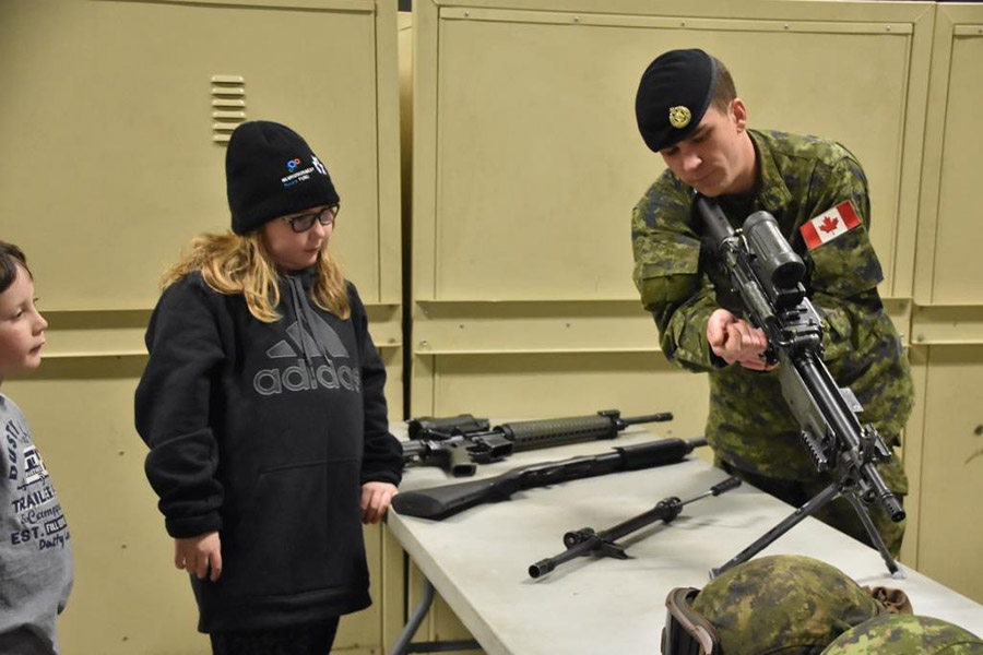 A soldier from the Lord Strathcona's Horse (Royal Canadians) Regiment teaches Rheanna Trepanier about different weapons that the unit uses.  