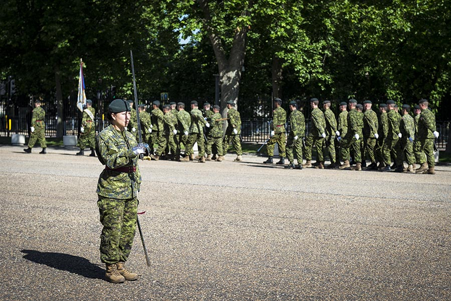 Captain Megan Couto, a member of 2nd Battalion, Princess Patricia's Canadian Light Infantry, stands at attention while troops march past at Wellington Barracks in London, England on June 13, 2017. Capt Couto had the privilege of being the first female infantry officer to lead the Queen's Guard on June 26.