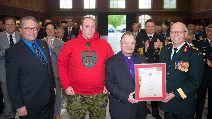 The Most Supportive Employer in the North award is presented to Bishop Larry Robertson of Yukon Diocese, Anglican Church of Canada at the Canadian Forces Liaison Council Awards Ceremony on 25 May, 2017 at the Cartier Square Drill Hall in Ottawa, Ontario. From left to right: Mr. David Connelly, Private Robert Langmaid, Bishop Larry Robertson and Brigadier-General Kelly Woiden.