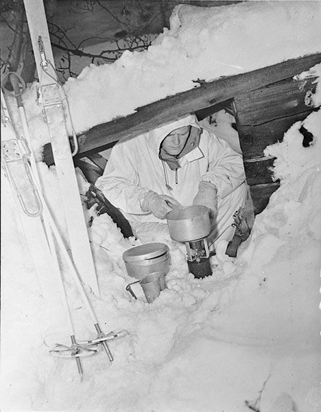 An unidentified member of the First Special Service Force preparing rations in an improvised shelter during cold weather survival training in Blossburg, Montana, January 1943.  