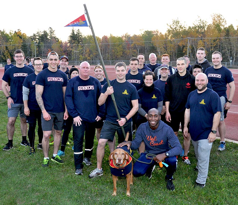 Members of 67th Depot Battery of The Royal Regiment of Canadian Artillery School with mascot Gunner (Canine) Loki, who won the first-ever Commandant's pennant challenge on the 20th of October, 2017, during an inter-Battery relay run that followed a 4 kilometre unit run. Photo: Bombardier Joseph Genereux, The Royal Regiment of Canadian Artillery School. ©2017 DND/MDN Canada.