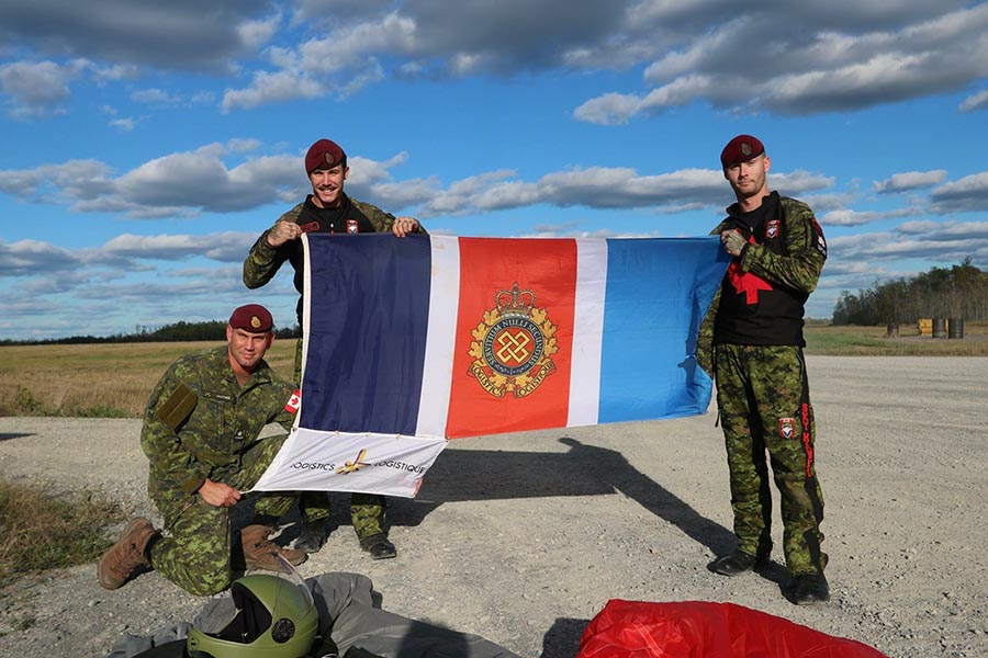 Logistics Officer Major Mathieu Gauthier (kneeling), along with parachute riggers Corporal Jason Bent and Master Corporal Jeremy Canfield proudly pose with the Logistics Branch 50th Anniversary Flag and Pennant at Trenton, Ontario in September, 2017 as part of a global flag relay in advance of the anniversary on February 1, 2018. Photo: ©2017 DND/MDN Canada.