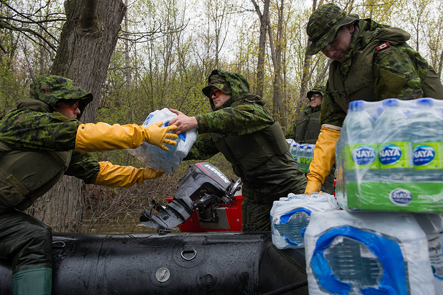 Reservists from 35 Canadian Brigade Group distribute water to residents on l'Île Mercier during Operation LENTUS, May 14, 2017. Assisting civilian authorities in responding to natural disasters is just one way Reservists serve. The Canadian Army Reserve is growing its ranks and offering, among other incentives, a Full-time Summer Employment Program. Photo: Corporal Myki Poirier-Joyal, Canadian Forces Base/Area Support Unit St-Jean. ©2017 DND/MDN Canada.