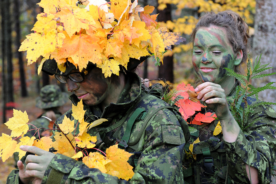 Candidate Heather Kitson (left) of Portage la Prairie, Manitoba, has her foliage adjusted by fellow course member Candidate Mercedes Pinch of Okanagan, British Columbia on October 17, 2013, prior to a stalking exercise at Camp Aldershot in Nova Scotia, in which the candidates have to advance on an observation position from 100 metres away without being detected. Photo: Warrant Officer Jerry Kean, 5th Canadian Division. ©2013 DND/MDN Canada.