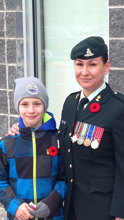 Just before attending the local Remembrance Day parade, Sergeant Marie-Eve Martin stands with her son Alex on November 11, 2015 at their home in Oromocto, New Brunswick.