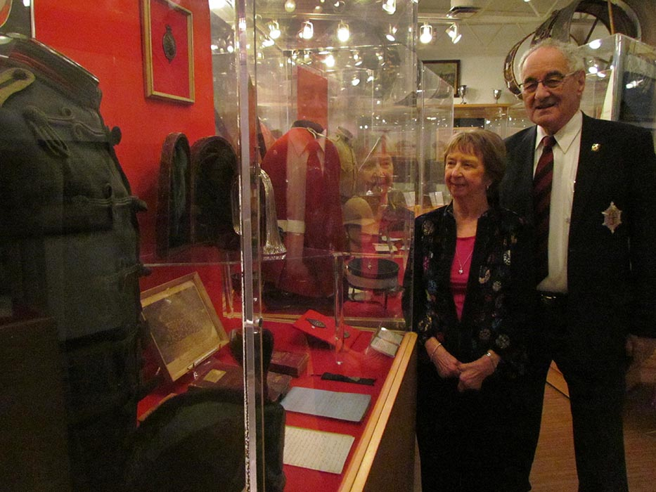 The co-curators of the Governor General's Foot Guards Regimental Museum stand among artifacts.