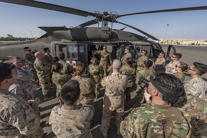 Sergeant Harrison Meyer from C Company (Medevac) 1-108th Assault Helicopter Battalion United States Army, explains how to load and unload a Blackhawk helicopter with Canadian Armed Forces medical personnel during Operation IMPACT in Kuwait